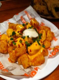 Lots of Tots from Hooters. Tater tots covered in cheese, bacon, chives, and sour cream.