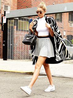 Mit Skaterrock, Croptop und weißen Sneakers, beweist Gigi Hadid, dass auch flache Schuhe zum femininen Look super aussehen.