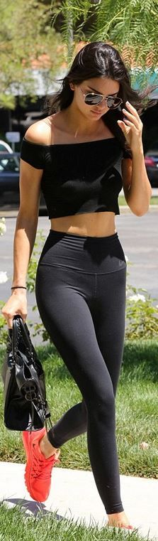 Who made Kendall Jenner's black pants, orange sneakers, aviator sunglasses, cropped top, and leather handbag?