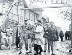 Liberated prisoners at Auschwitz concentration camp helping their buddy to walk out through the infamous gates with a help of Soviet doctor.