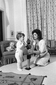 Jackie & Son John: American First Lady Jacqueline Bouvier Kennedy (1929 - 1994) kneels on the floor with her son, John F. Kennedy, Jr. (1960 - 1999), playing with a wooden toy figure, inside the White House, Washington, D.C. There is a rag doll on the chair behind them. (Photo by John F. Kennedy Library/John F. Kennedy Library/Getty Images)