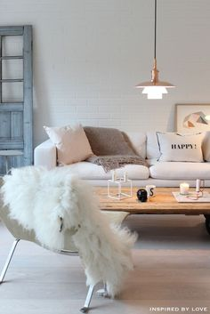 A modern living room with a sofa and white cushions, a pendant light, a setting chair with nice white rug in top of chair. http://www.urbanroad.com.au/
