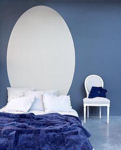 De ovale vorm van de rugleuning van de traditionele witte medaillonstoel komt terug op de blauwe muur.