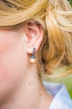 """Die Perle aus Eschenholz ist mit einer Sterlingsilber-Blüte eingefasst. Akzente von Schmucksteinen im Baguette-Schliff verleihen dem Design noch mehr Eleganz, sodass die """"Blütenparadies""""-Ohrringe für alle festlichen Anlässe einfach perfekt passen."""