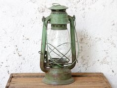 Original green vintage storm lanterns and lamps with a wonderful usd patina. Vsit our site today. Rustic Lanterns, Vintage Lanterns, Storm Lantern, Work Lamp, Retro Lighting, Mason Jar Lamp, Shades Of Green, Color Splash, Light Colors
