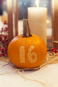 Rustic Green Orange and Ivory Autumn Wedding - Bright orange pumpkins used as table numbers ♥