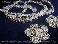 Tiara tipo losangos com 1,20 cm e 2 flores retas de 5 petalas com 6 cm cada, folheada em ouro branco, com strass e perolas de qualidade. R$350,00