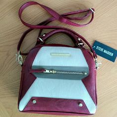 """Steve Madden?Red Small Satchel/Crossbody Bag Featuring deep, luxuriously red wine and cream color. So gorgeous and adorable!  Dual rolled handles,  a longer, detachable shoulder strap is included, it can be put as a sling/crossbody bag. Goldtone hardware. Top zipper closure Exterior - front zippered pocket, stud detail, back name plate Interior - lined with signature fabric. It has boasts back wall zip pocket, brand logo patch, and two slip pockets.  Measurement (apx) 9.5"""" x 9"""" x 3.25"""" 3.5?…"""