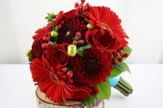 Red is classic and never goes out of style. We mixed deep Red Dahlias, Gerbera Daisies, and Tea Roses with Hypericum Berries for texture and depth.  Flowers by A Floral Affair - www.afloralaffair.com. #Wedding #Flowers #AFloralAffair