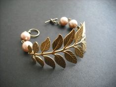 "this beautiful bracelet is made with a flexible gold plated brass leafy frond, beautiful bronze glass pearls strung on antiqued brass wire make up the rest of the bracelet.  it's closed with a toggle clasp  the bracelet measures 7.5"" long   thank you"