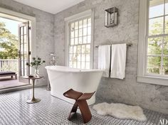 In the East Hampton, New York, home of publishing-world powerhouses Pilar Guzmán and Chris Mitchell, the Carrara-marble-lined master bath is accented with a vintage Sori Yanagi stool | archdigest.com