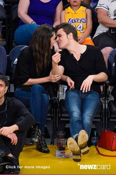 Phoebe Tonkin (L) and Paul Wesley kiss at a basketball game between the Atlanta Hawks and the Los Angeles Lakers at Staples Center on March 15, 2015 in Los Angeles, California. (Photo by Noel Vasquez/GC Images)