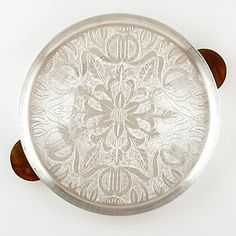 """Our Les Indiennes Metal Tray boasts a glorious etched floral motif and handsome wood handles for easy handling. Use this handcrafted 15.75"""" tray indoors or out during dinner parties for serving everything from aperitifs to dessert."""