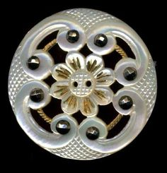 19th c. carved pearl button with openwork and cut steels riveted to a textured brass ring.