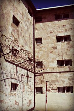 the formidable limestone walls, cell windows & razor wire of Fremantle prison