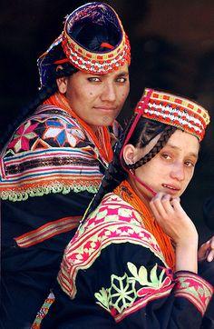 Two Kalash women pose on their veranda in Rumboor Valley, one of the three Kalash valleys