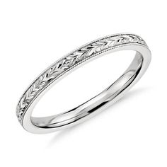 Exquisitely hand-engraved, this wedding ring features an intricate motif in 14k white gold.