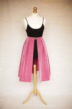 A SKIRTTAIL is a unique, handmade decorative over-skirt that can be worn over the top of any dress or any skirt/top combination that you already have on. It is worn high on the waist and fastened neatly with a gold clasp. The gap in the centre of the fabric elegantly reveals the garment that you have on underneath, instantly updating your outfit. Rose pink Mid-length available on Etsy.