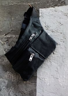 Casual handmade black waxed canvas hip bag with two zipped pockets and side pocket.
