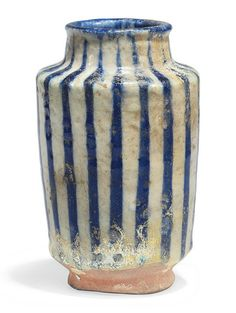 AN INTACT KASHAN POTTERY ALBARELLO  CENTRAL IRAN, 12TH CENTURY. Of typical form with slightly flaring walls on short ring foot, with short neck and rounded lip, the decoration with cobalt-blue lines on white ground, with old inventory number to foot