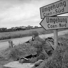 IWM caption : THE BRITISH ARMY IN THE NORMANDY CAMPAIGN 1944. Lance Corporals A.Burton and L.Barnett of 6th Airborne Division guarding a road junction near Ranville, 7 June 1944. Each is armed with a Mk V Sten submachine gun. Horsa gliders can be seen in the background.