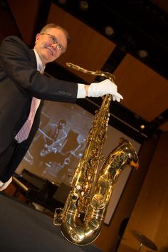 Smithsonian Receives John Coltrane Saxophone to Kick Off Jazz Appreciation Month, John Hasse, Curator of American Music at the Smithsonian, with white gloves carefully holds Coltrane's Selmer Mark VI tenor saxophone.
