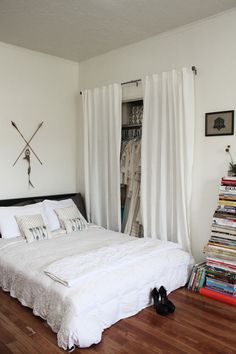 studio apartment configuration--bed almost right next to the closet, books stacked with a vase on top. #cute