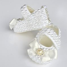 Our signature Itty Bitty Toes pearly slippers. White baby shoes with pearls all sewn by hand. Offered by Itty Bitty Toes - Children's Boutique Clothing!