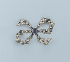 A BELLE EPOQUE SAPPHIRE AND DIAMOND BOW BROOCH  Designed as a ribbon bow, finely pavé set with cushion-shaped and rose-cut diamonds centering millegrain-set lines of calibrated sapphires divided by seedpearls, an octagonal cut sapphire at the centre, circa 1910