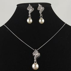 14k Gold Filled Austrian Crystal White Pearl Necklace and Earrings $10.99  Beautiful Pearl and Austrian Crystal Necklace Set.  This set is great for that special occasion whether it be out for cocktails or going to a school prom.  This set adds dazzle to your attire.  Material:  Sea Shell Pearl, Austrian Crystal, Gold Filled  Necklace length: 18 ¾ inches  Necklace pendant length: 1 ¾ inches x 1 ¾ inches, Pearl diameter: 0.47 inch  Earring size: 1 ¾ inches x 0.59 inch, Pearl diameter: 0.39…
