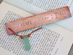 By The Sea Bookmark - A lightly weathered copper book mark with a pretty drop of knotted natural leather and sea glass.  With a rustic sea shore driftwood feel to it, this bookmark has 'my heart sleeps by the sea' stamped onto it.  Our range of individual bookmarks make the perfect gift for friends, family and colleagues. Each bookmark is hand-crafted by designer Nicola Jones