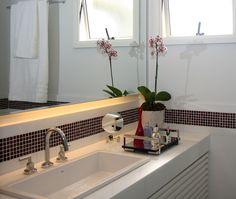 Detalhe em banheiro feminino. Revestimentos em nanoglass branco e pastilhas de murano na cor marsala. Decoração aposta nos acessórios espelhados e na marcenaria planejada com pintura branca. Projeto de design de interiores para apartamento de 70 m2 em São Paulo.