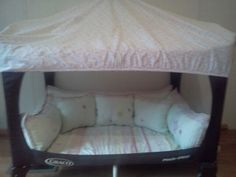 A nook made out of a pack n play with throw pillows made out of a bumper pad...