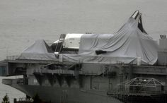 The space shuttle Enterprise is draped with cloth that had protected it before Superstorm Sandy passed though, leaving the spacecraft shrouded on the deck of the Intrepid Sea, Air & Space Museum, at its dock on the Hudson River in New York, Tuesday, Oct, 30, 2012. Sandy, the storm which was downgraded from a hurricane just before making landfall, caused multiple fatalitiehalted mass transit and cut power to more than 6 million homes and businesses. (AP Photo/Peter Morgan)