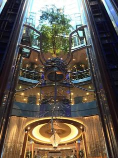 Standing hundreds of feet tall in the Grand Foyer, the atrium tree is a majestic sight. Designed by artist Bert Rodriguez, this grand installation represents a tree reflecting in the water—mirroring the theme of the ship.