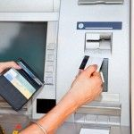 Cash withdrawal. Womans hand inserting plastic card Visa into the ATM