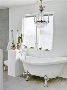 Dreamy bathroom with window, chandelier and tub