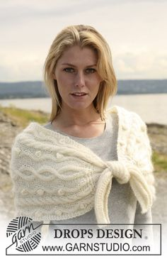 """Knitted DROPS shoulder piece with cables, tied at the front in """"Alpaca"""" and """"Vivaldi""""."""