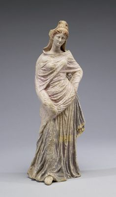 "Standing Draped Maiden. The willowy shape and the draping of the fabric on top of the maiden's high, ""melon"" hairstyle are typically South Italian. The statuette was originally brightly painted. 3rd century BCE (Hellenistic). Terracotta with white slip, traces of paint and gilt. 13 3/4 x 4 1/2 x 3 7/16 in. (35 x 11.5 x 8.7 cm). Via the Walters Museum"