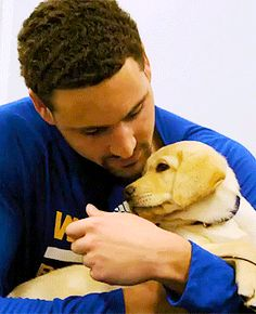 Klay Thompson playing with a service puppy in training named Klay