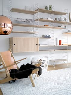 white wall- and floor panels. white magazine shelf. shelves, work desk and cabinet in oak.