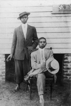 auntada:    Claude Hudson and Lonnie Montgomery, in suits and hats, pose for a photo beside a house. One sits in a chair, the other stands behind.  Los Angeles, California  ca. 1926  Shades of L.A.: African American Community