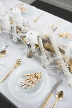 an all white ghostly halloween tabletop with bone and candle centerpiece runner | coco kelley