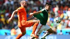 Oribe Peralta of Mexico and Ron Vlaar of the Netherlands compete for the ball
