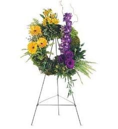 """Ring of Hope Wreath  This wreath, warmly decorated in memory of a loved one lost will bring comfort to family and friends. One wreath with a moss and foliage base features clusters of gerberas, alstroemeria, delphinium and lisianthus and arrives on an easel.  Approximately 15"""" D http://www.pjsflowers.com/ring-of-hope-wreath/"""