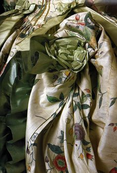 Back (detail) of a Robe a la Polonaise, Chinese painted silk | c. 1770's.  The material is draped into pre-arranged folds then stitched and concealed by green silk rosettes.  Seventeenth and eighteenth century fashion in detail. London: V&A Press. pp. 66-67.