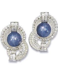 A PAIR OF ART DECO STAR SAPPHIRE AND DIAMOND CLIP BROOCHES Of swirl design, each set with a cabochon star sapphire, within a circular-cut diamond panel with baguette-cut diamond shoulders, to the vari-cut diamond scrolling motif, mounted in platinum, circa 1930