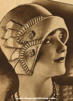 1929 Lido Hat: Charming face looks its best under the chic silhouetted lines of this model. Suave lines copied from a high-priced import, in a pleasingly soft, good quality wool felt. Shaped in low helmet fashion at sides; close-cropped at back for utmost coat-collar ease. The soft-rolling, graduated brim is clipped in two-tab effect at side and edged with finely plaited grosgrain ribbon matching the band with cut loop ends. Double-ended rhinestone pins flash from tabs.