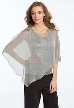 If you're shopping for a party look but not keen on wearing a dress to your event, you'll love this blouse by JR Nites. Features include a sequin lace tank with an iridescent chiffon asymmetrical cape. It's just the right amount of shimmer for that special occasion. And you'll adore the rhinestone pin detail on the shoulders. Pair this lovely top with tailored trousers or a chic knee skirt. Accessorize this with a pair of heels, a classic clutch bag and gorgeous jewelry. • Scoop neckline…