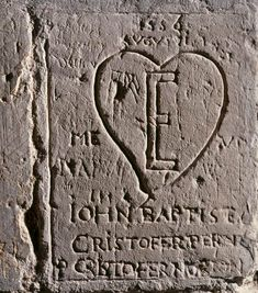 """In this graffiti in the Salt Tower, the """"E"""" within the heart stands for Elizabeth Tudor. The grafitti was carved by Giovanni Battista Castiglione, Italian tutor to Elizabeth from 1544 onward, and was imprisoned in the Tower by Queen Mary I in 1556. He survived, and upon Elizabeth's accession to the throne in 1558, Castiglione was made a Groom of the Privy Chamber, a position he held until right before his death."""